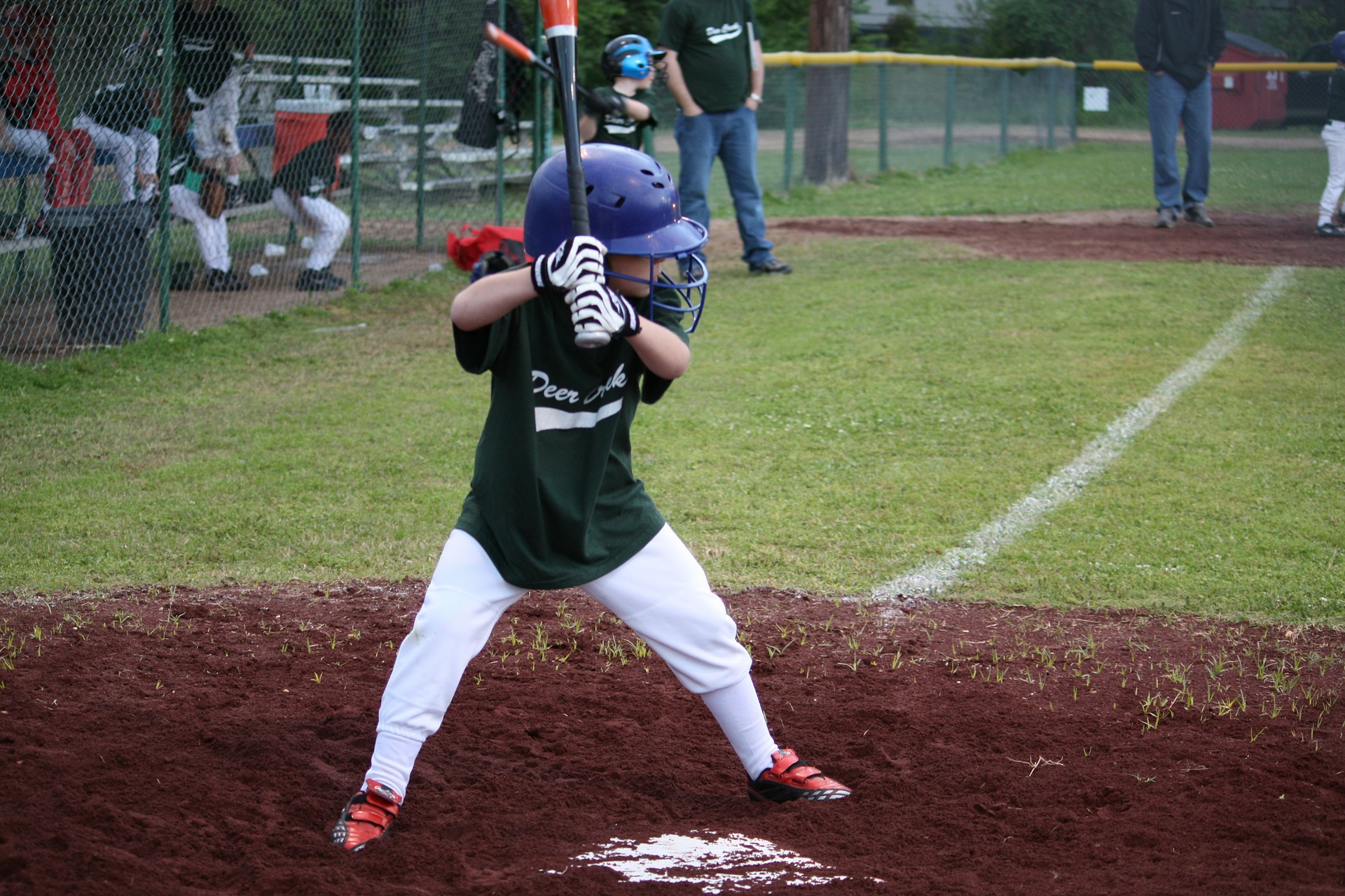 Image: a child steps up to the baseball plate ready to swing the bat