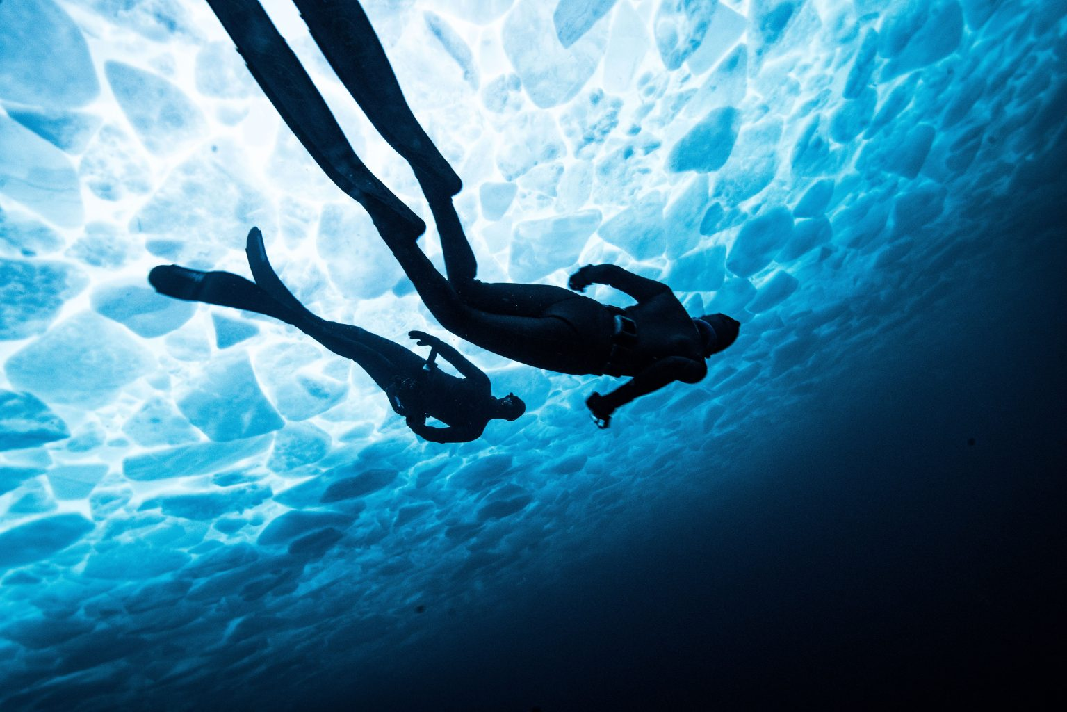 Image: Two freedivers swimming under glowing ice