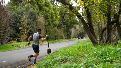 Image: Beau Miles running with a shovel during his mile an hour day