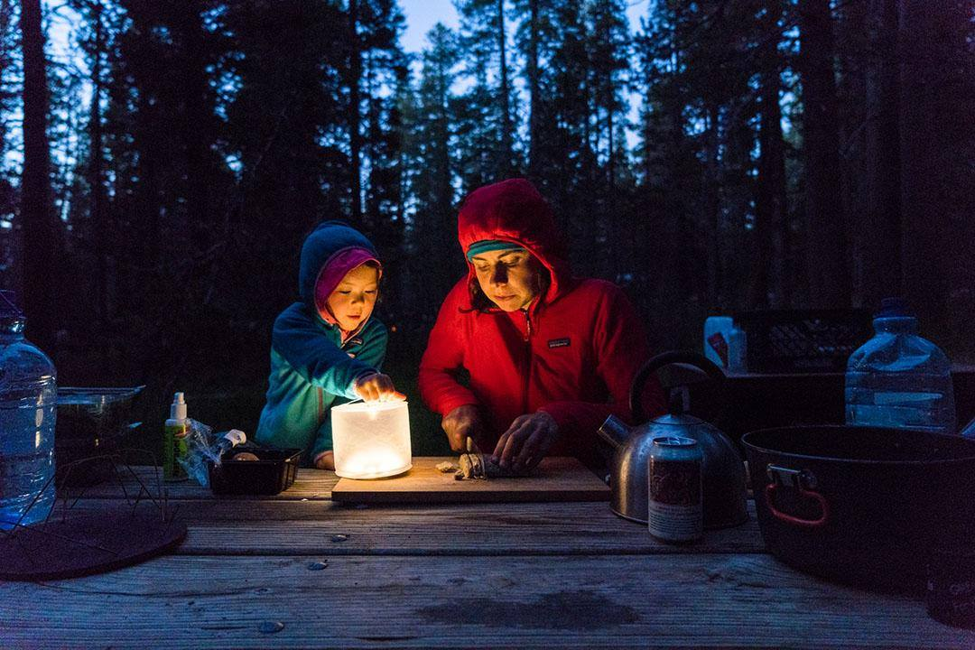 Image: Mother and child make dinner while camping