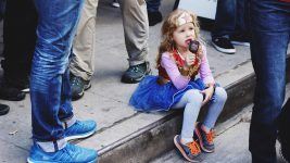 Image: Young kid in a superhero costume eating ice cream on the curb!