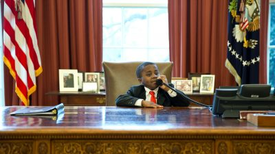 Image: A young Kid President sitting behind the desk in the Oval office.
