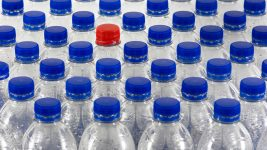 Image: Plastic water bottles with blue caps and one bottle with a red cap