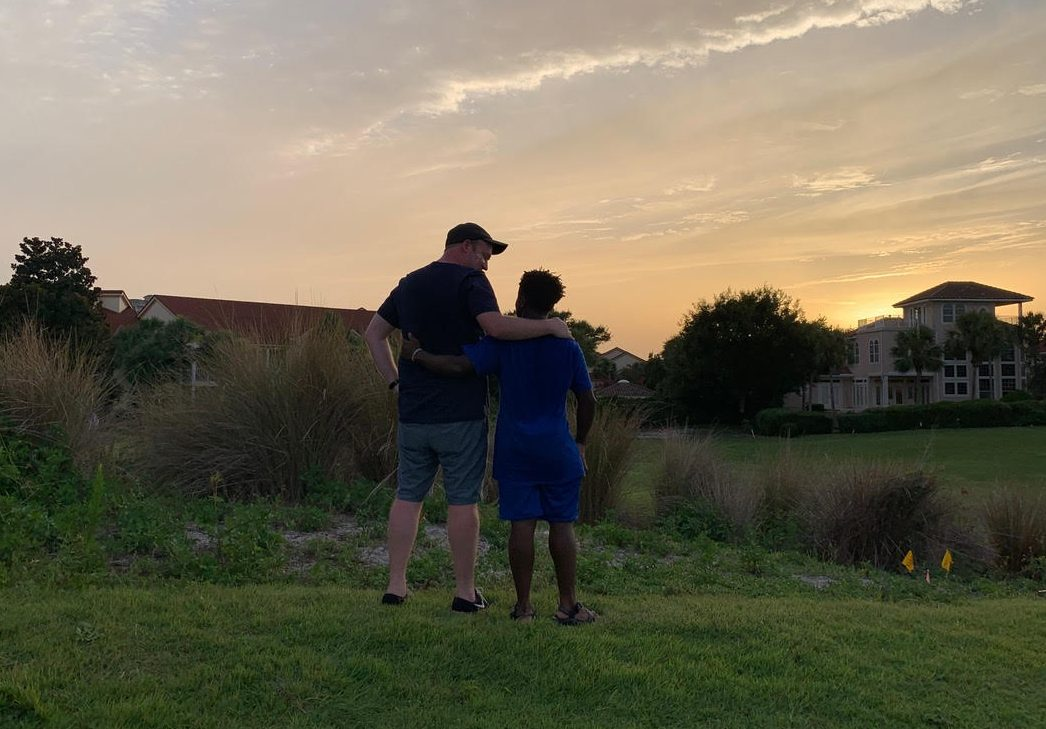 Image: Brad and Robby embracing, with their backs to the camera, watching the sunset