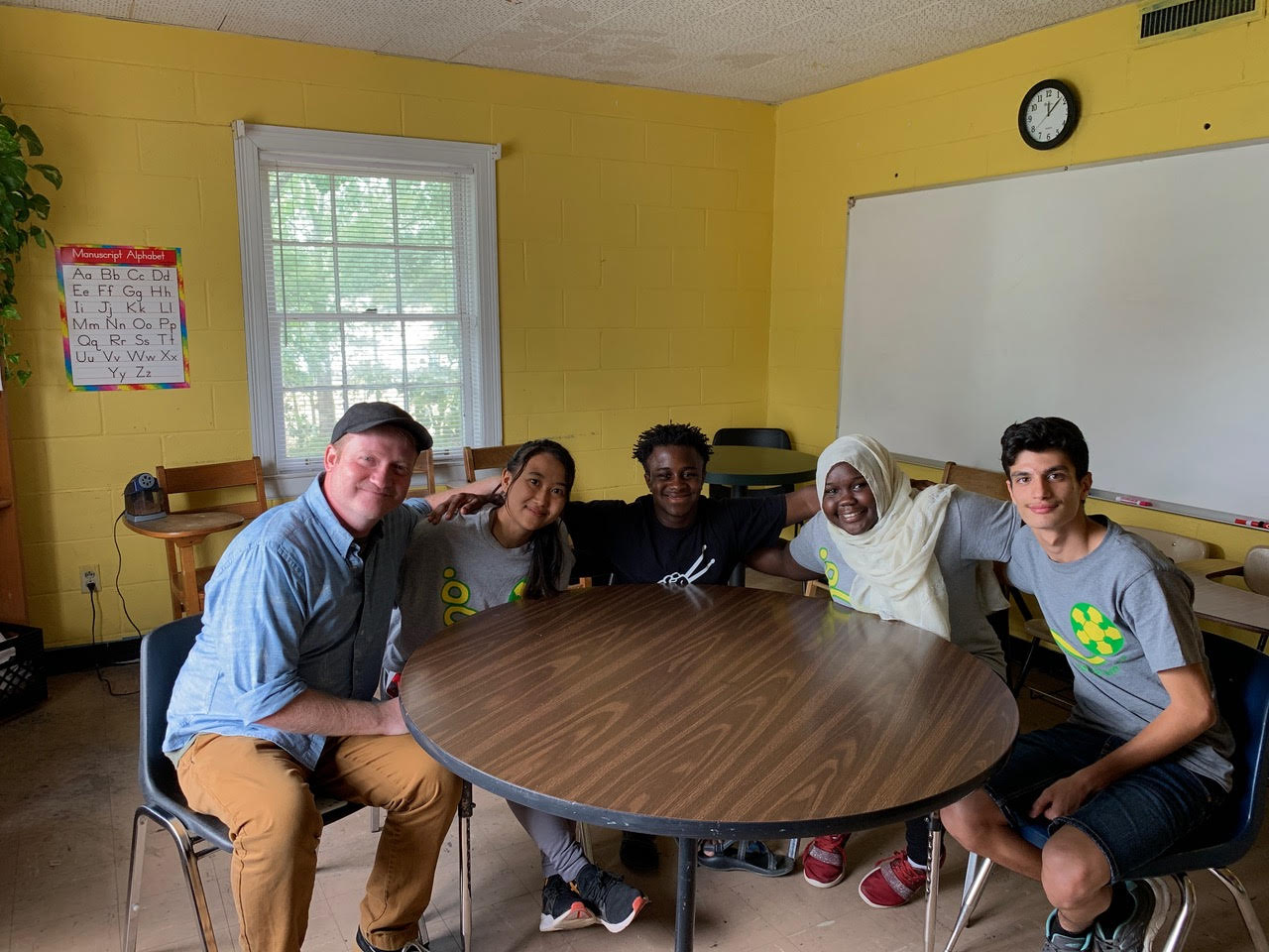 Image: Brad and Robby around a table with students from Fugees Academy