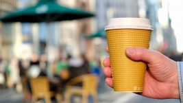 Image: Hand holding a to-go cup of coffee