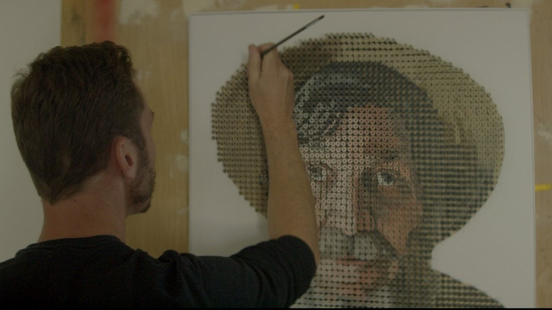 Image: Artist Andrew Meyers painting the portrait of George Wurtzel that's made of nails.