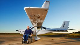 Image: Dave Jacka in his wheelchair in front of his plane