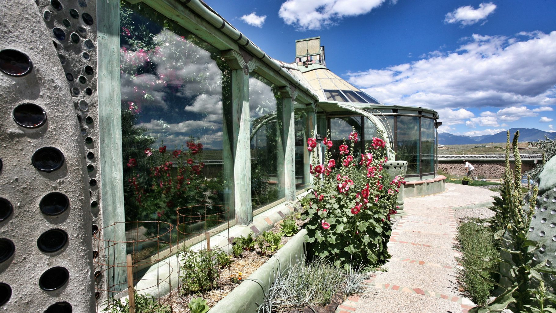 Image: View along the outside wall of an Earthship. Plants are seen growing inside and out!