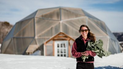 Image: Intern standing outside in the snow with greens from their greenhouse!