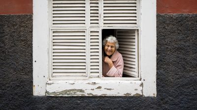 Image: Elderly woman peering out her shuttered windows smiling!