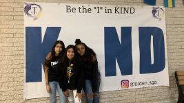 "Image: Tilden Middle School Students in front of a poster that says ""be the I in kind"""
