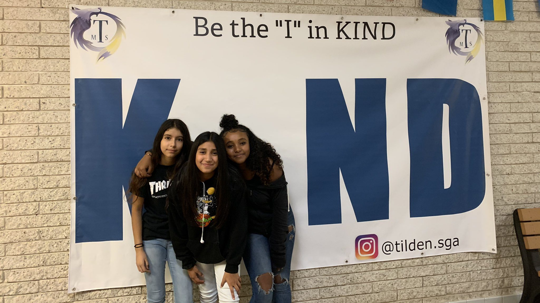 """Image: Tilden Middle School Students in front of a poster that says """"be the I in kind"""""""