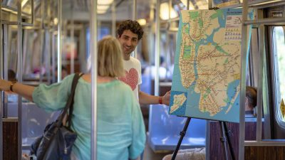 Image: Marco Santini on the NYC subway asking a woman what she loves about New York City