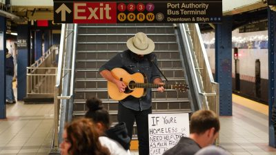Image: Busker (Will) playing guitar in the middle of a subway station with his head tilted down, next to the sign.