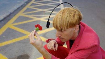 "Image: Neil Harbisson using his antenna to ""see"" the color of the flower he's holding in front of himself"