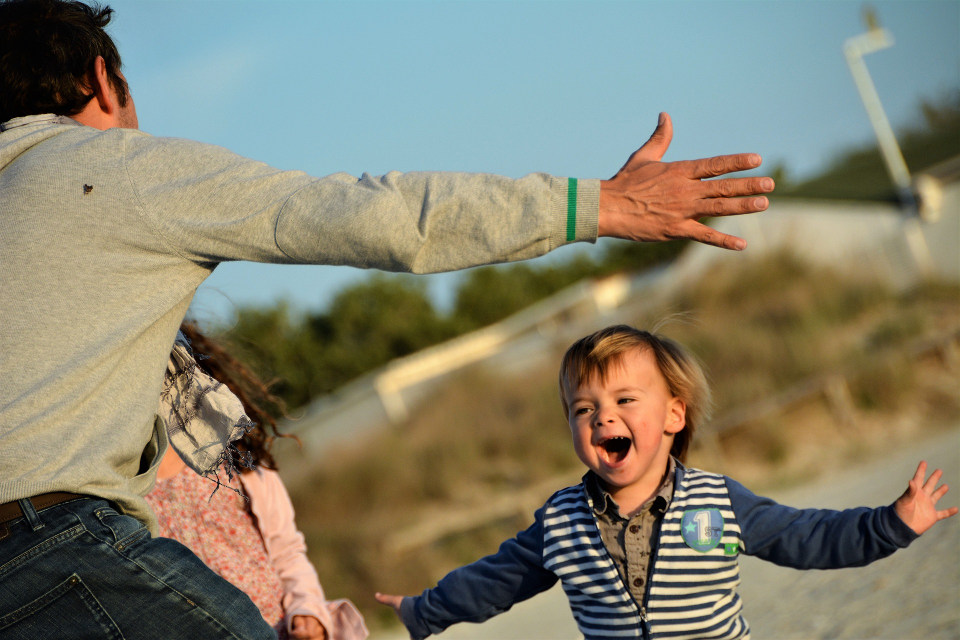 Image: boy runs toward his father's outstretched arms