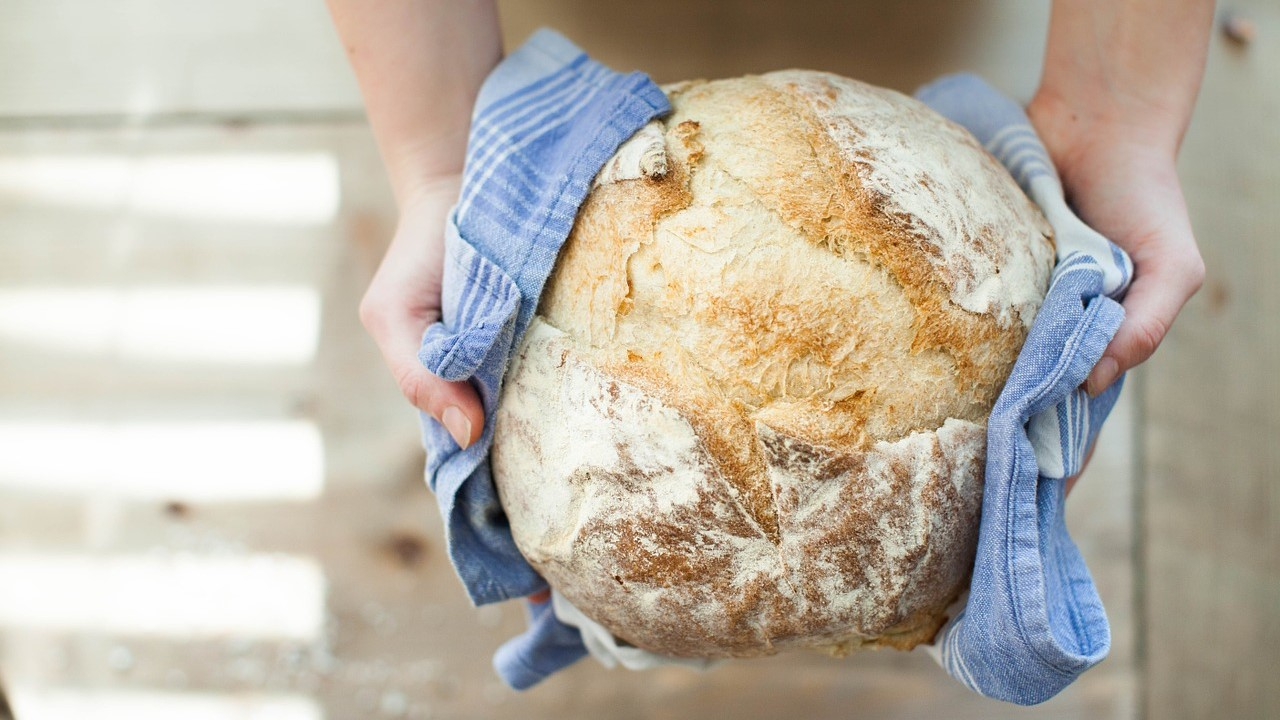 Image: A loaf of bread being gently held out in a towel