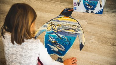 Image: Young child putting together a jigsaw puzzle shaped like a penguin