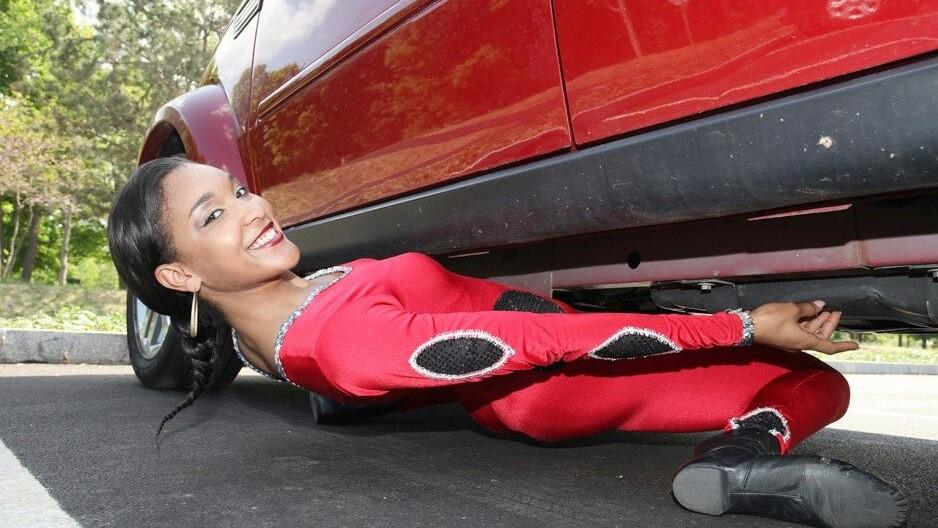 Image: Shemika Charles shimmying under an SUV