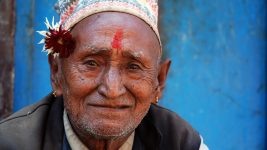 Image: Elderly man with a flower tucked behind his ear