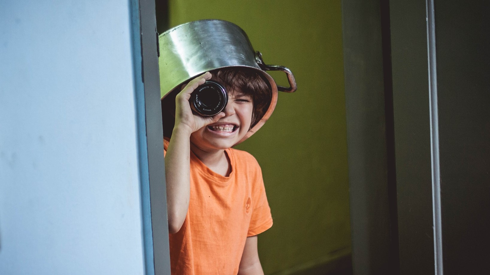 Image: child wearing a kitchen pot on their head, peeking around the corner with a camera lens as a telescope