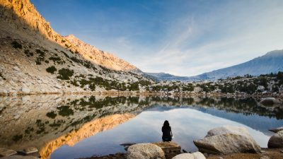 Image: Woman meditating by a mountain pond with a big sky before her.
