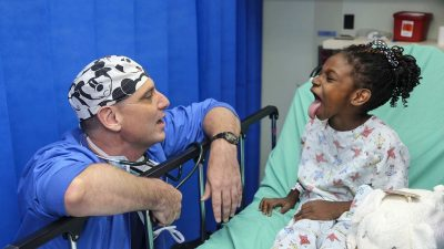 Image: Doctor sitting next to a hospital bed, wearing blue scrubs and a Mickey Mouse patterned head cap, interacting with a young girl who's sticking her tongue out. Feeling is joyful!