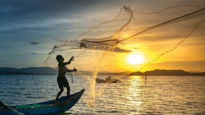 Image: Man throwing a fishing net at sunset