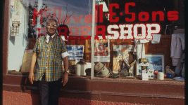 Image: Older gentleman stands in front of his barber shop