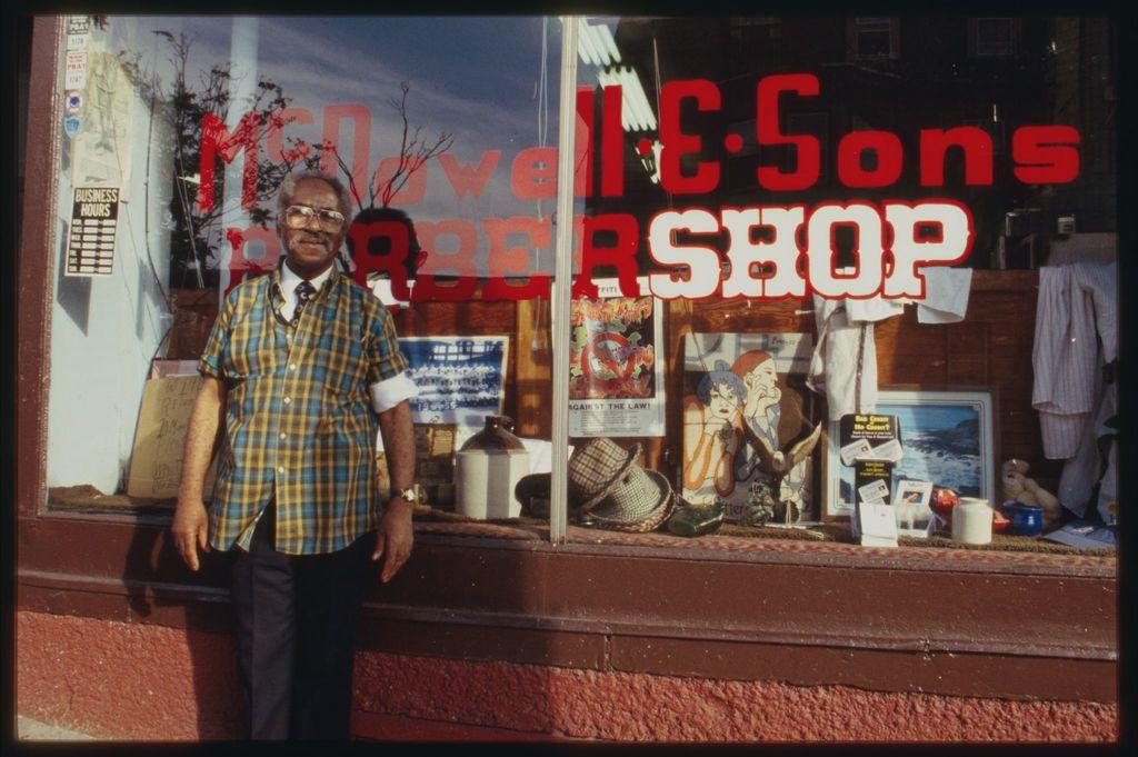 Image: Older gentleman stands in front of his barber shop