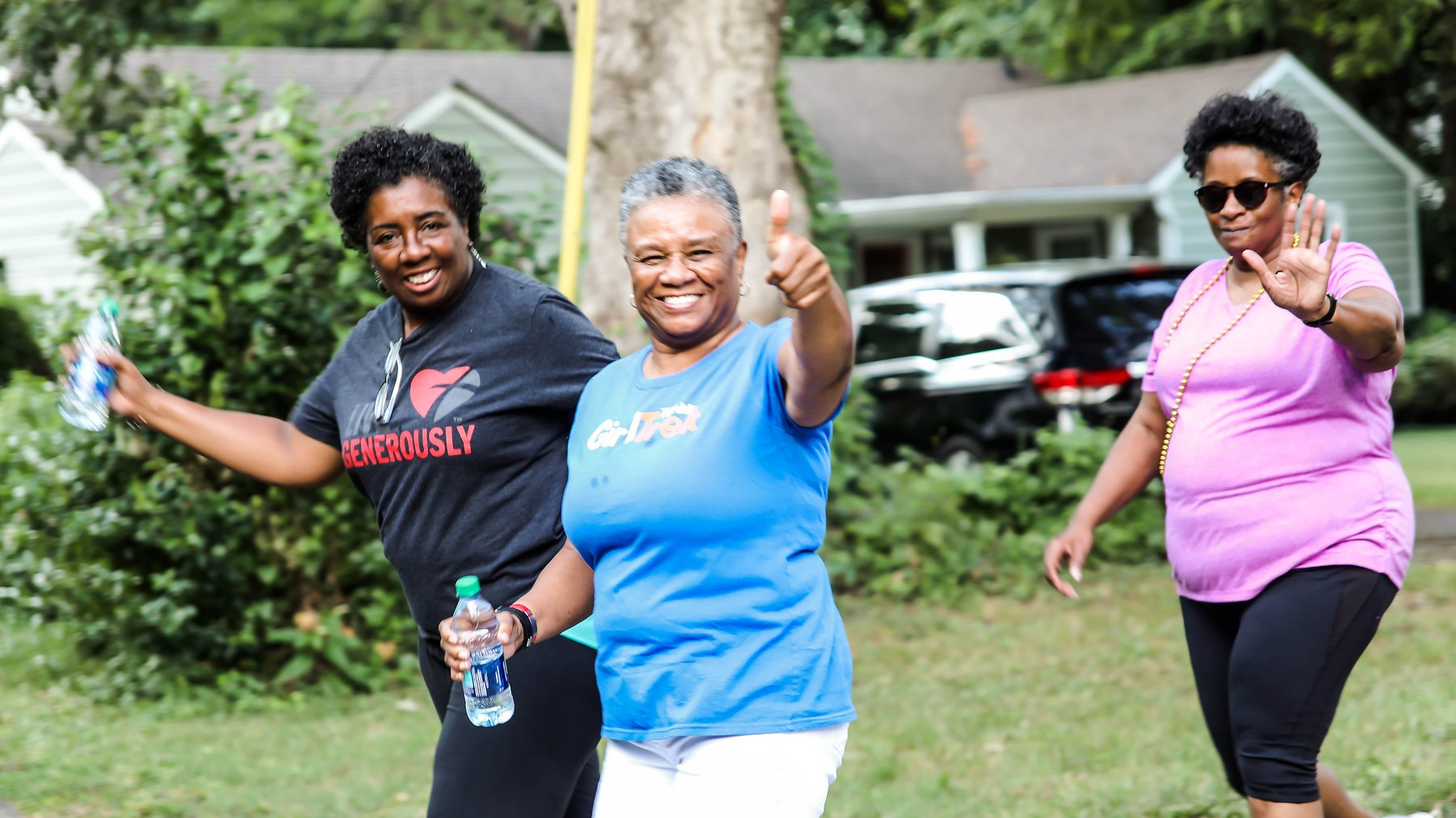 Source: Three older women smiling walking in a neighborhood with GirlTrek. One is giving a thumbs up, the others are waving