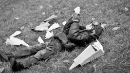Image: Young child laying in the grass with paper airplanes all around him