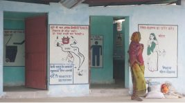 Image: woman walking outside of a SHRI bathroom facility
