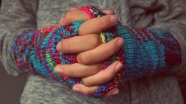 Image: Woven Hands Wearing Knit Gloves