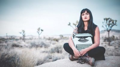 Image: Afrose Fatima Ahmed sitting on a rock in Joshua Tree holding her typewriter!