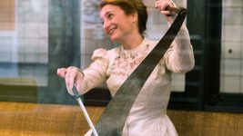 Image: Nataliz in a white gown smiling and playing the musical saw!