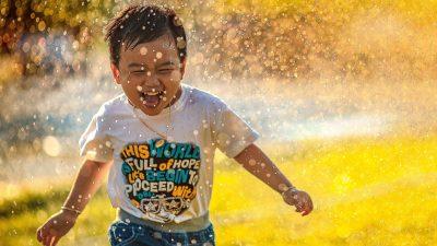 Image: kid smiling and running in sprinklers