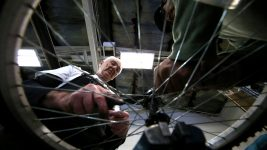 Image: older person working on a bike at the Fort Collins Bike Shop