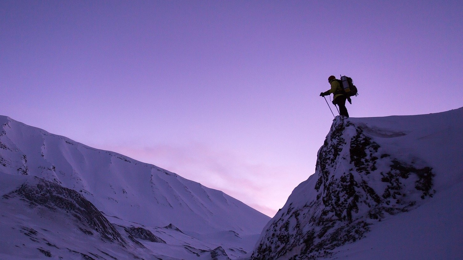 Image: Person with large backpack on standing atop of a snow covered cliff, staring off into the distance.