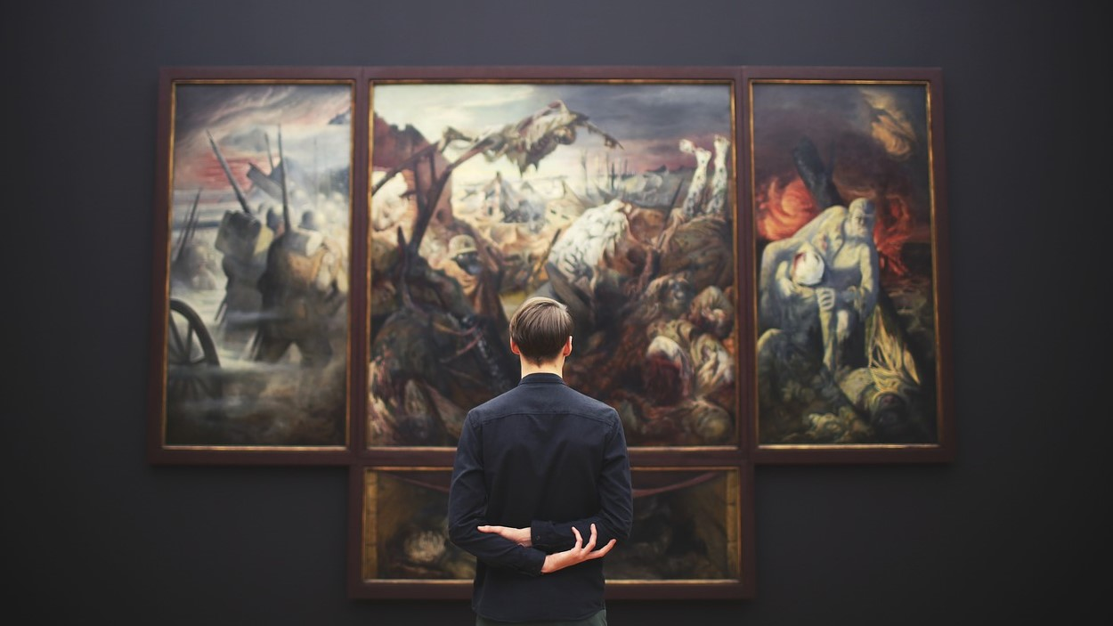 Image: person standing infront of a large painting with their hands behind their back