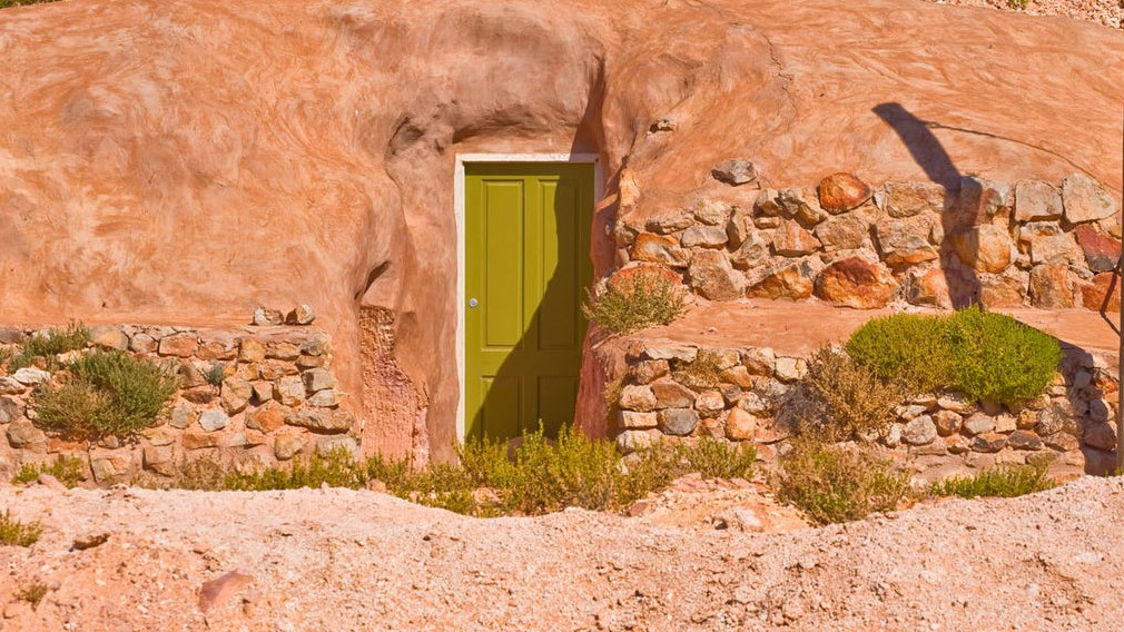 Image: Green door in the sandstone—an entrance to an underground home in Coober Pedy