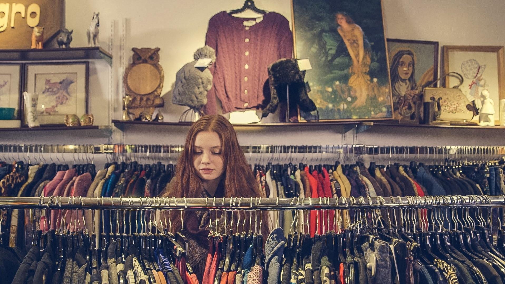 Image: woman sifting through clothing racks at a vintage clothing store