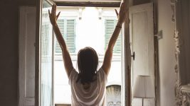 Image: Person raising their arms with joy to the morning sun at their window