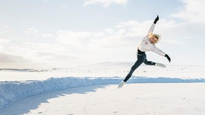 Image: Emmi Peltonen jumping in the air in the arctic rink