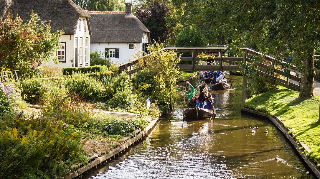 Image: People on boats going down a canal in Giethoorn