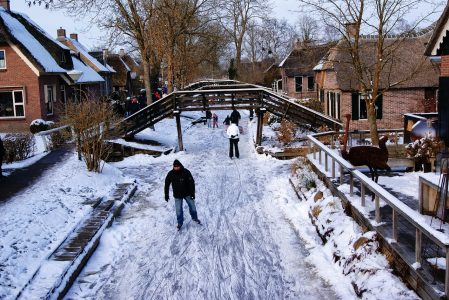 Image: People ice skating down the frozen canals in Giethoorn