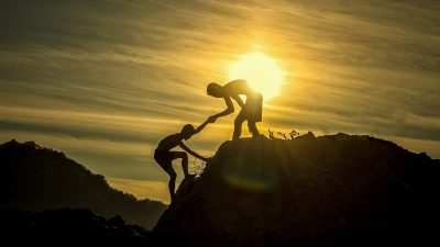 Image: two people on a hill, one is helping the other up