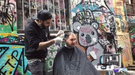 Image: The Streets Barber giving a haircut outside, next to a wall covered in beautiful graffiti