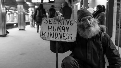 """Image: Man holding a sign that says """"seeking human kindness"""" in a Boston subway platform"""
